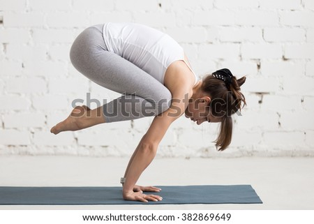 Beautiful young woman working out indoors, doing yoga exercise on blue mat, handstand asana, exercise for arms and wrists strength, Crane (Crow) Pose, Bakasana with arms straight, full length - stock photo