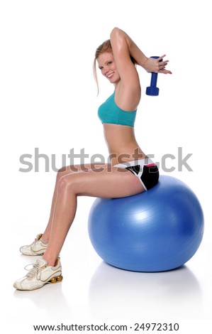 Beautiful young woman working out with dumbbell sitting on fitness ball - stock photo