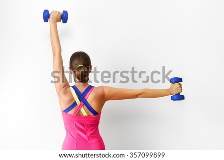 Beautiful young woman working out with dumbbells in fitness gym on a gray background