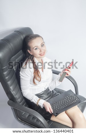 Beautiful young woman working with a laptop in the room. Young Businesswoman Using Laptop Over White - stock photo