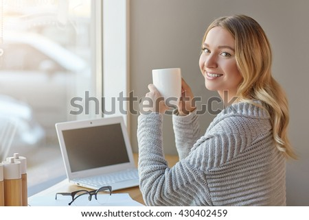 Beautiful young woman working with computer at cafe, holding cup and looking at camera. Freelancer