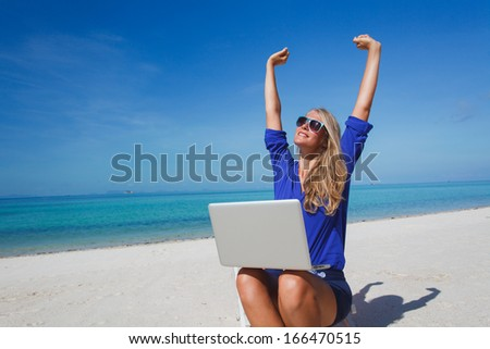 Beautiful young woman working with laptop on the tropical beach - stock photo