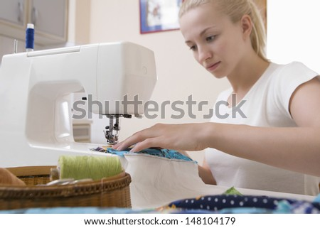 Beautiful young woman working with sewing machine at home