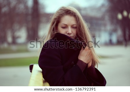 Beautiful young woman wrapped in a coat from the cold
