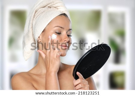 Beautiful , young woman wrapped in towel spreading cream on her face, shot on white background, - stock photo