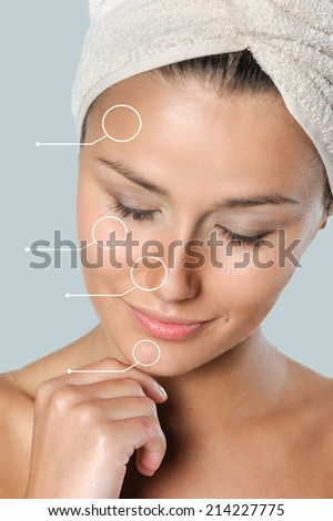 Beautiful , young woman wrapped in towel touching her chin with hand - stock photo