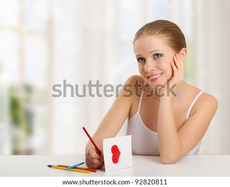 beautiful young woman writes a love letter - a card for valentines day in the room - stock photo