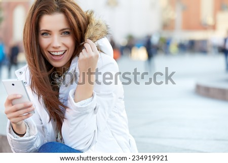 beautiful young woman writing a message. Smiling girl. Winter
