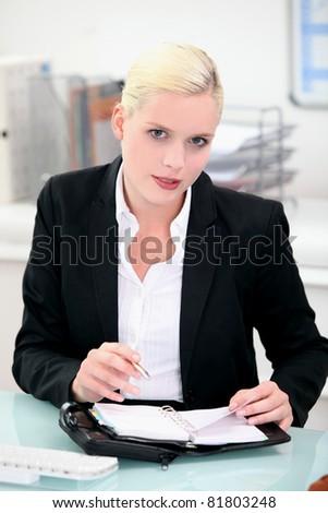Beautiful young woman writing on organizer - stock photo