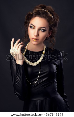 Beautiful young woman. Young girl. Girl in leather clothes. Portrait on a dark background. Beauty portrait. Toned image - stock photo