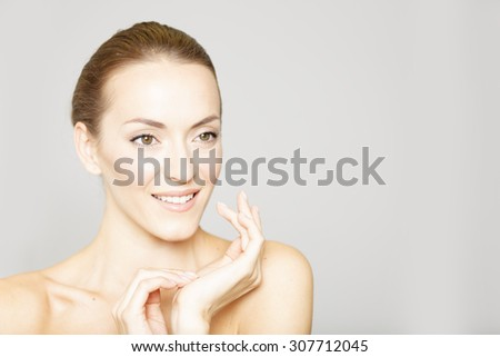 Beautiful young womans face with her hand resting on her chin and neck in a beauty style pose