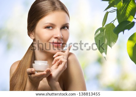 beautiful young women advertising  a herbal cosmetics cream on natural blurred background - stock photo