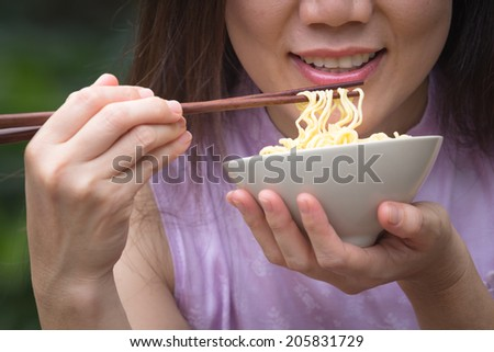 Beautiful young women are eating asian noodle