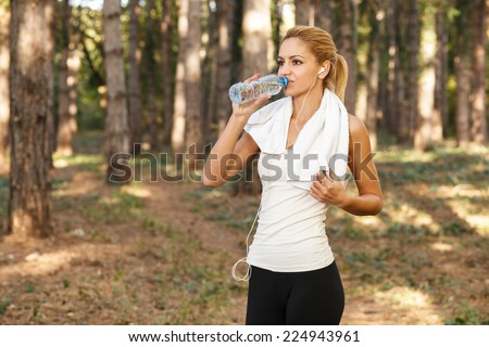 Beautiful young women drinking water after running - stock photo