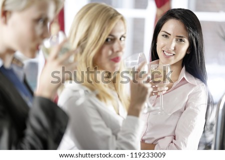 Beautiful young women enjoying a glass of wine after work at a bar. - stock photo