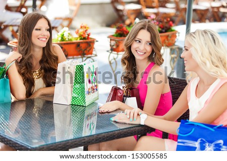 beautiful young women friends in cafe on a terrace after the shopping - stock photo