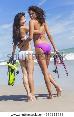 Beautiful young women girls in bikinis with diving equipment on a beach  - stock photo