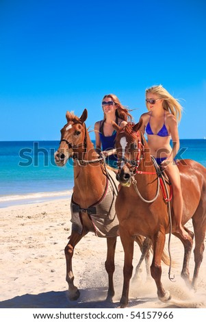 Beautiful young women horse riding on a tropical beach
