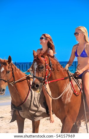 Beautiful young women horse riding on a tropical beach - stock photo