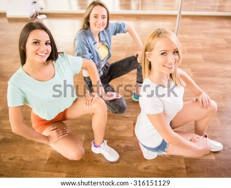 Beautiful young women in dance studio are posing and smiling to the camera. - stock photo