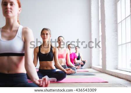 Beautiful young women in sports clothing while sitting at lotus position.