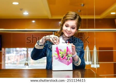 Beautiful young women in the cafe pulled out a white gift box - stock photo