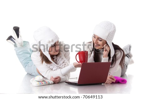 Beautiful young  women in winter clothes with laptop lie on a white background.