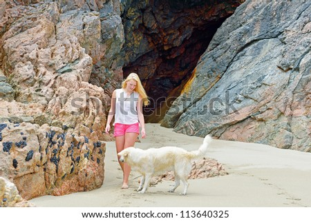 Beautiful young women with dog on the beach
