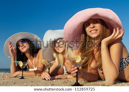 Beautiful young women with fruit cocktail relaxing on beach - stock photo