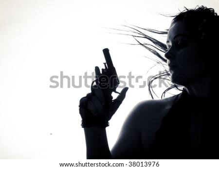 Beautiful young women with gun. Isolated. low-key - stock photo