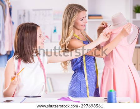 Beautiful young women with measuring tape on shoulders working at pink dress on mannequin in studio.