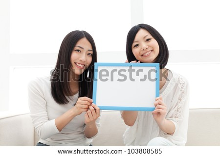 Beautiful young women with message board. Portrait of asian. - stock photo