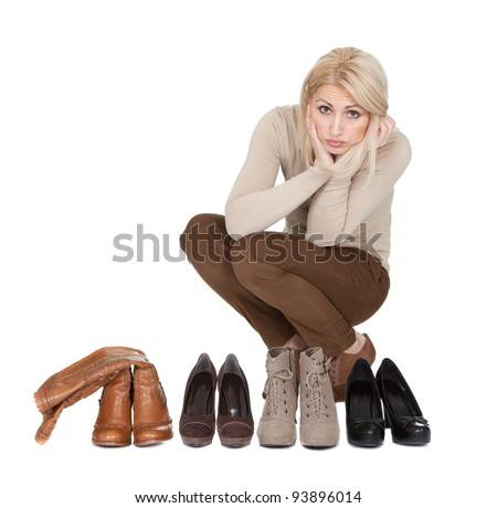 Beautiful young woomen choosing shoes to wear. Isolated on white - stock photo