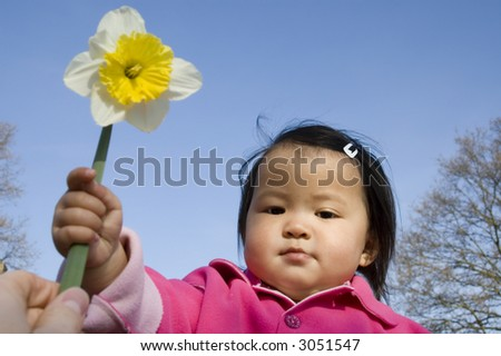 beautifull asian girl holding a daffodil (narcissus) flower - stock photo