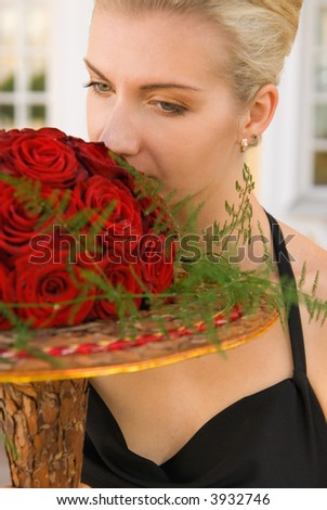 Beautifull blond girl with a bouquet of red roses