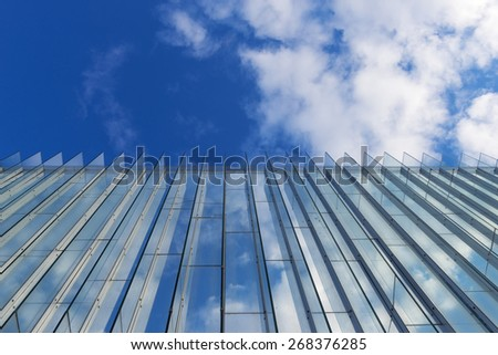 Beautifull blue cloudy sky reflected in a glass wall facade of a tall modern building - stock photo