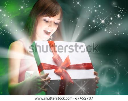 Beautifull girl opening x-mass magic present. Christmas - stock photo