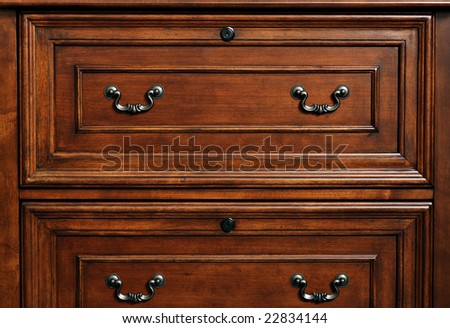 Beautifully crafted wood furniture. Detail of closed drawers with ornate pewter handles. - stock photo