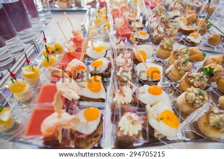Beautifully decorated catering banquet table with different food snacks and appetizers with sandwich, caviar, fresh fruits on corporate event or wedding celebration - stock photo