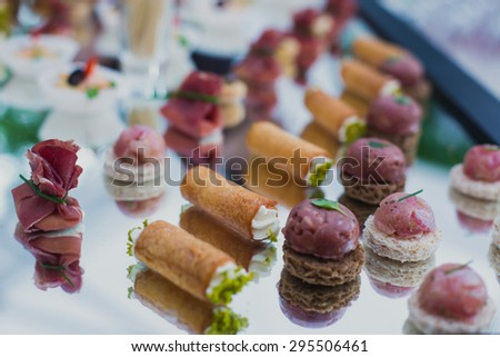 Beautifully decorated catering banquet table with different food snacks and appetizers with sandwich, caviar and fresh fruits on corporate party event or wedding celebration