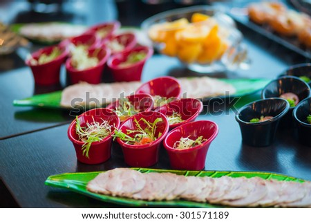 Beautifully decorated catering banquet table with different food snacks and appetizers with sandwich, caviar, fresh fruits on corporate party event or wedding birthday celebration - stock photo