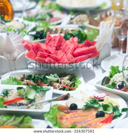 Beautifully decorated catering banquet table with different food snacks and appetizers with sandwich, caviar, fresh fruits on corporate birthday party event or wedding celebration  - stock photo