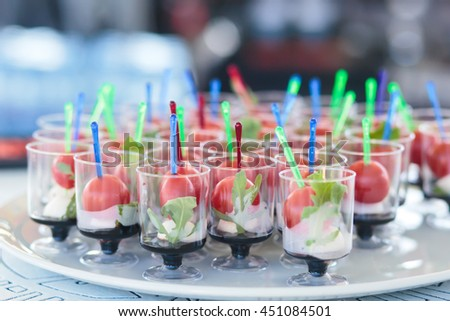 Beautifully decorated catering banquet table with different food snacks and appetizers with sandwich, caviar, fresh fruits on corporate birthday kids party event or wedding celebration - stock photo