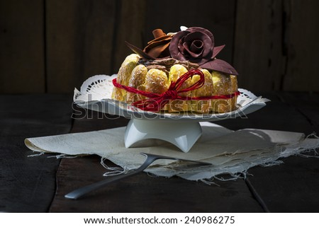 Beautifully decorated chocolate cake topped with roses on cocoa icing and surrounded with freshly baked golden pastries for a delicious dessert or sweet - stock photo