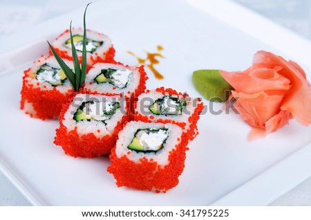 Beautifully decorated sushi on a plate with wasabi. Sushi on a plate with wasabi and ginger.  Six sushi rolls on a plate. Sushi with caviar, rice and egg. - stock photo