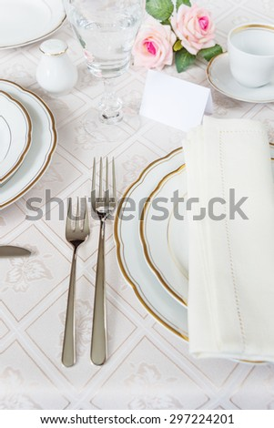Beautifully decorated table with white plates, crystal glasses, cutlery and flowers on luxurious tablecloths, with guest card - stock photo