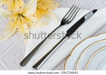 Beautifully decorated table with white plates, crystal glasses, linen napkin, cutlery and flowers on luxurious tablecloths - stock photo