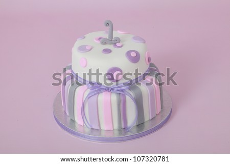 Beautifully designed and decorated girls double tier round birthday party cake with white fondant icing and purple and pink stripes and circular polka dots with number one isolated on pink background - stock photo