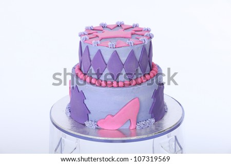 Beautifully designed and decorated two double tier princess themed birthday cake with purple and pink butter and fondant icing featuring beads shoes crown and diamonds on clear acrylic bar stool stand