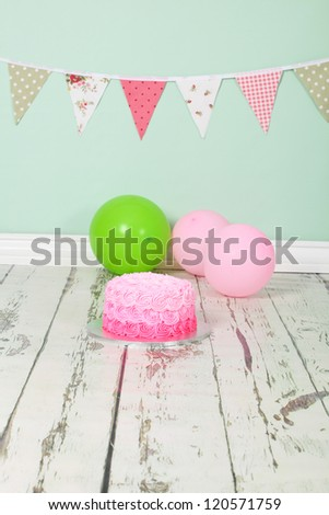 Beautifully designed pink ombre butter icing birthday party cake on distressed wooden white washed floor and green background with green and pick flag bunting and balloons